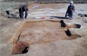 Two archaeologists sit behind excavated feature.