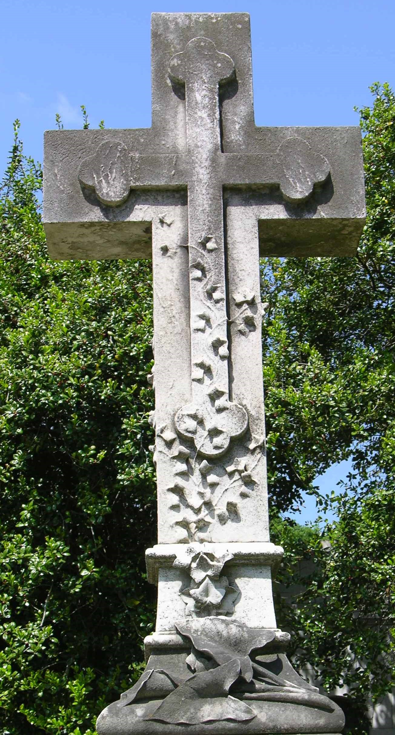 A marble cross monument with vines and leaves carved wrapping up from the base.