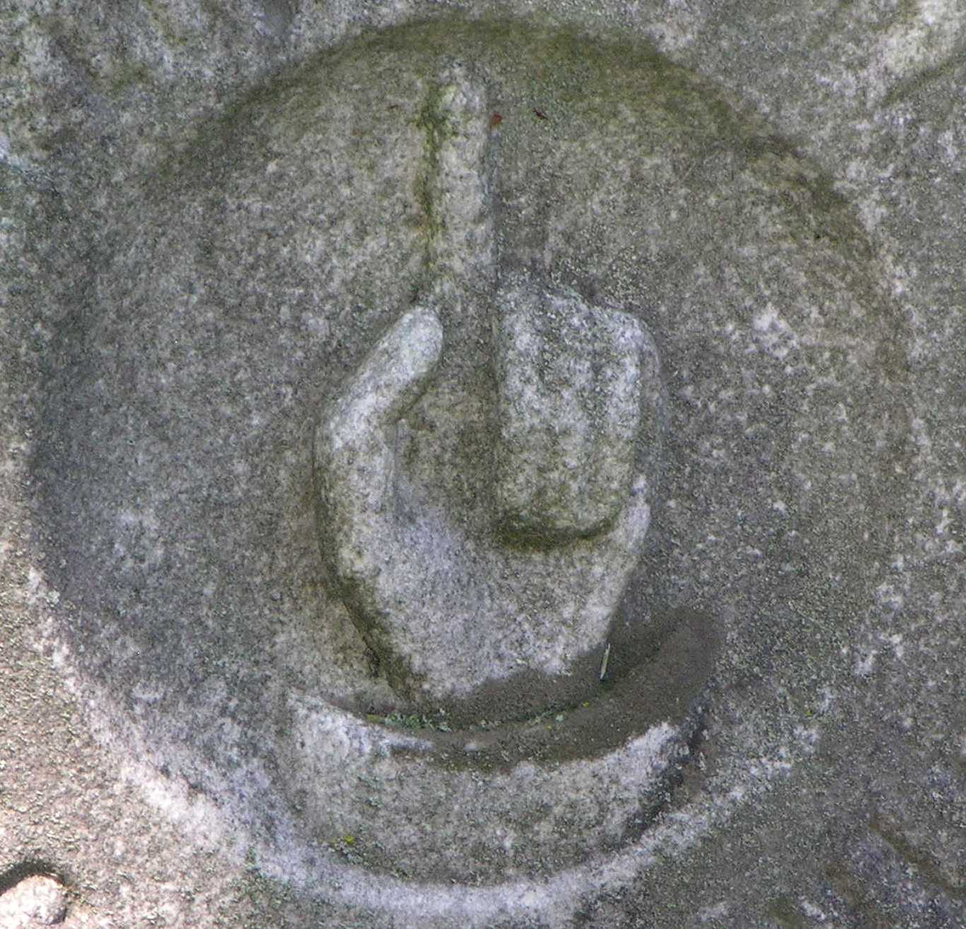 Marble carving of a hand with index finger pointing up.