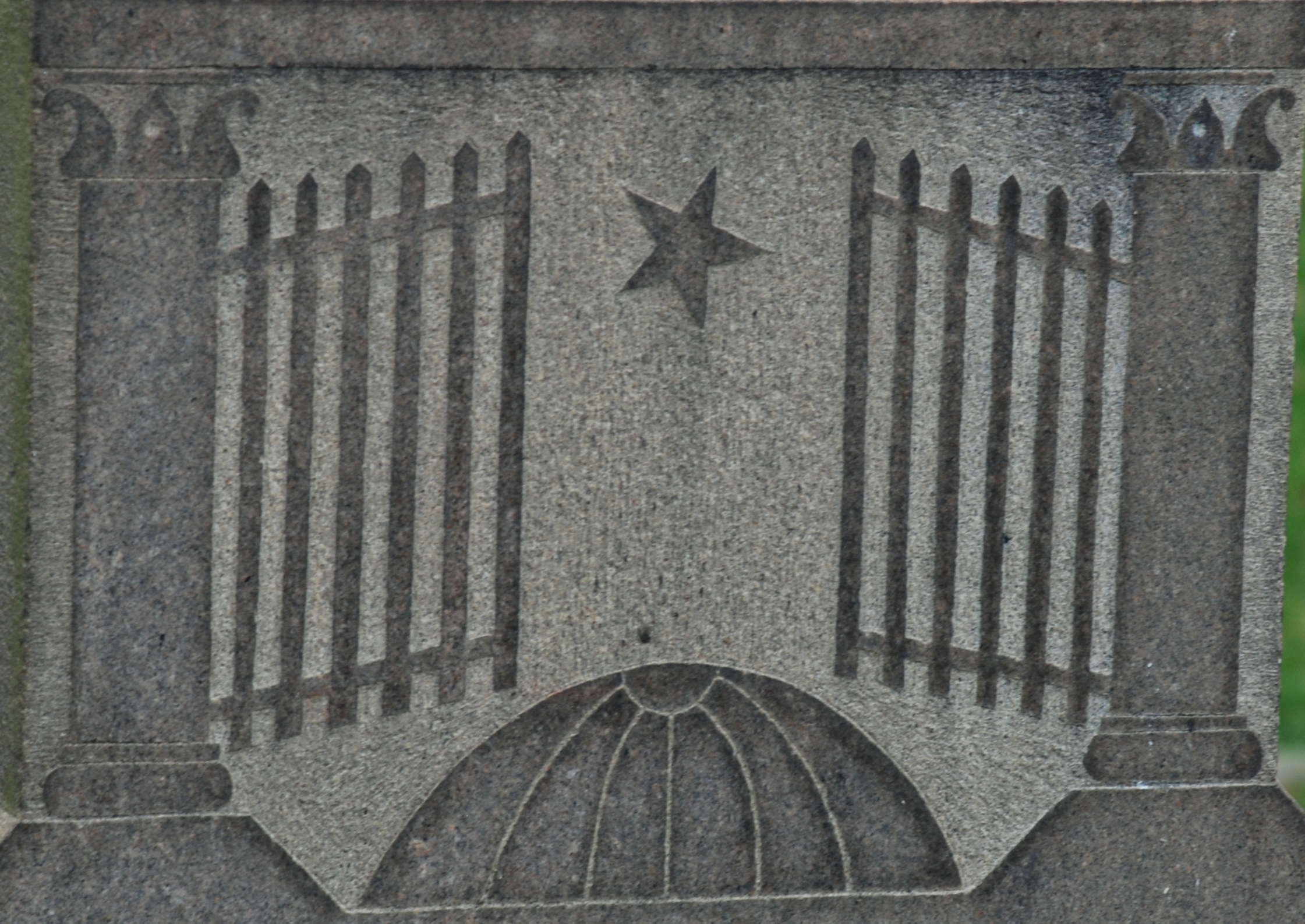 Granite carving of the gates of heaven opening to reveal a star, with earth below.