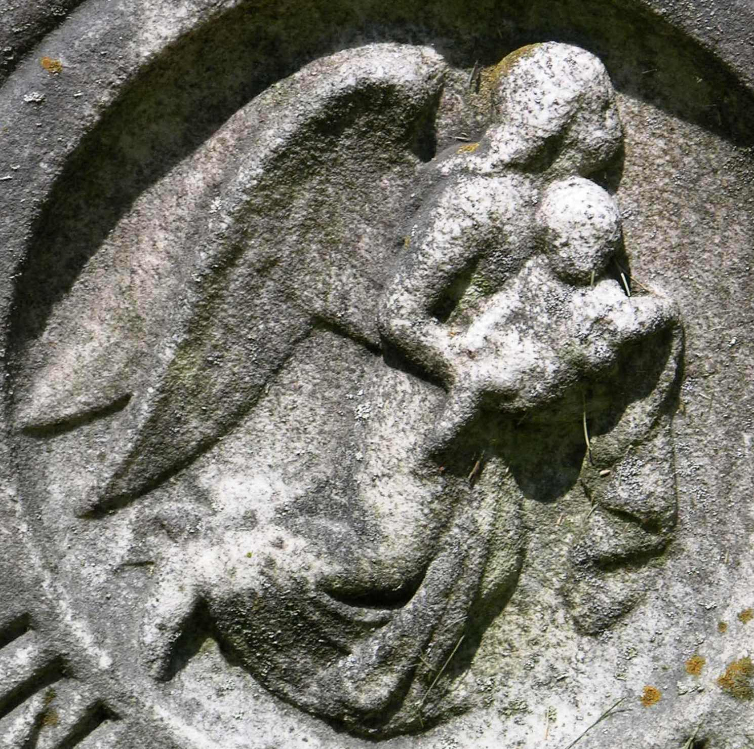 A carving of an angel carrying a child.
