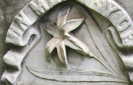 "A lily carved in marble beneath ""In Memory Of"" banner."