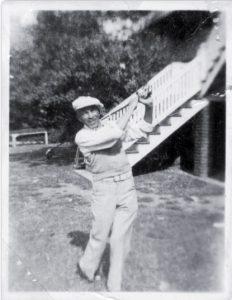 Photo shows Alexander swinging golf club.