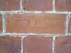 A brick in a Paxton House exterior wall, with the neatly inscribed initials AJP