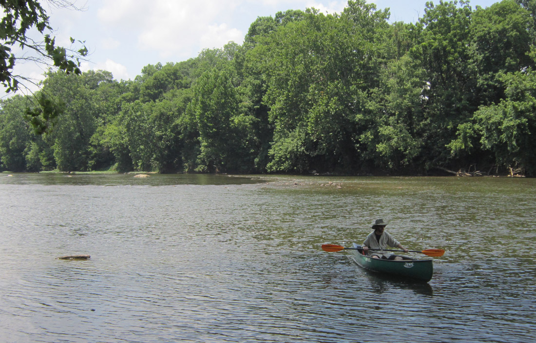Archaeologist canoeing on river.