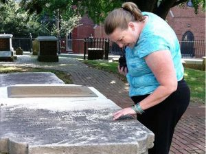 DHR Conservator Katherine Ridgway inspecting a stone at St. John's Church in Churchill, Richmond.