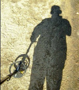 Ground shadow of a person metal detecting.